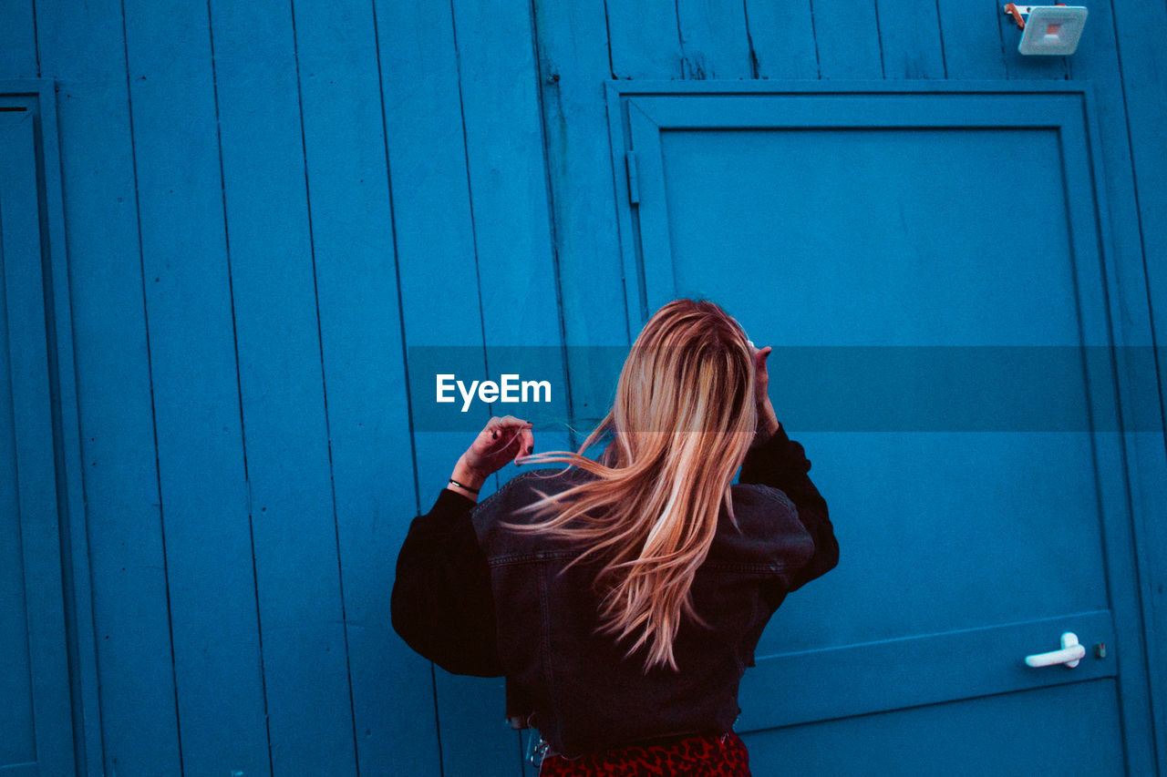Rear view of woman standing against blue wall