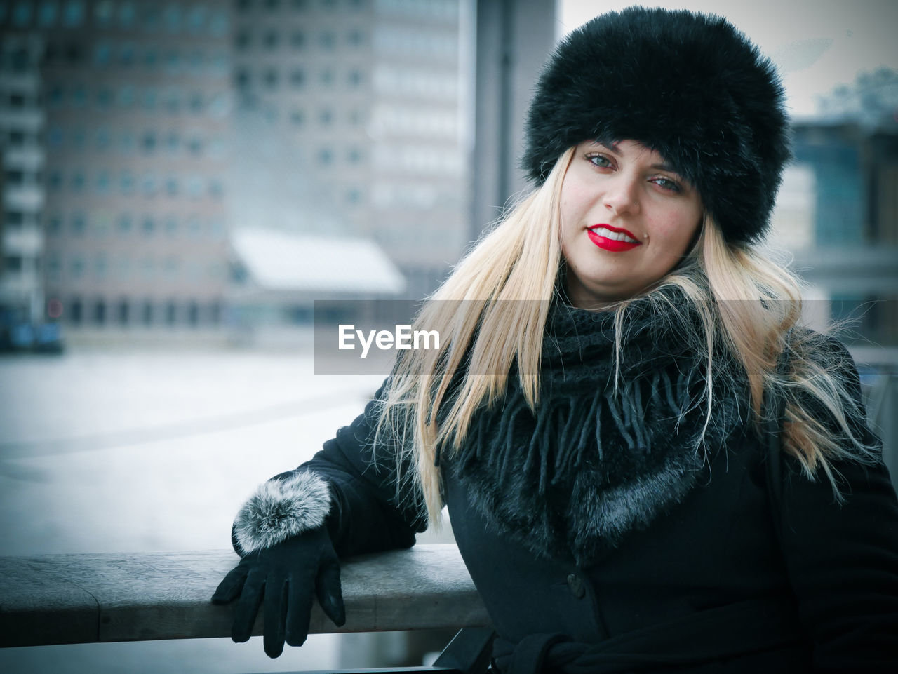 Portrait Of Young Woman In Fur Hat Standing Against Buildings