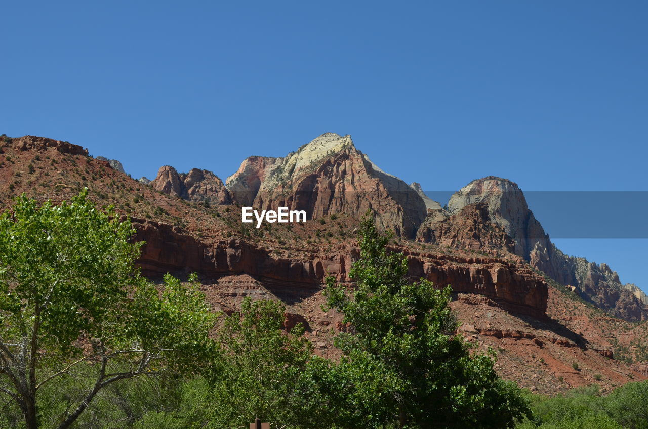 sky, clear sky, mountain, rock formation, nature, scenics - nature, rock, beauty in nature, tranquil scene, rock - object, blue, day, tranquility, copy space, travel destinations, no people, plant, non-urban scene, travel, solid, outdoors, formation, ancient civilization, eroded