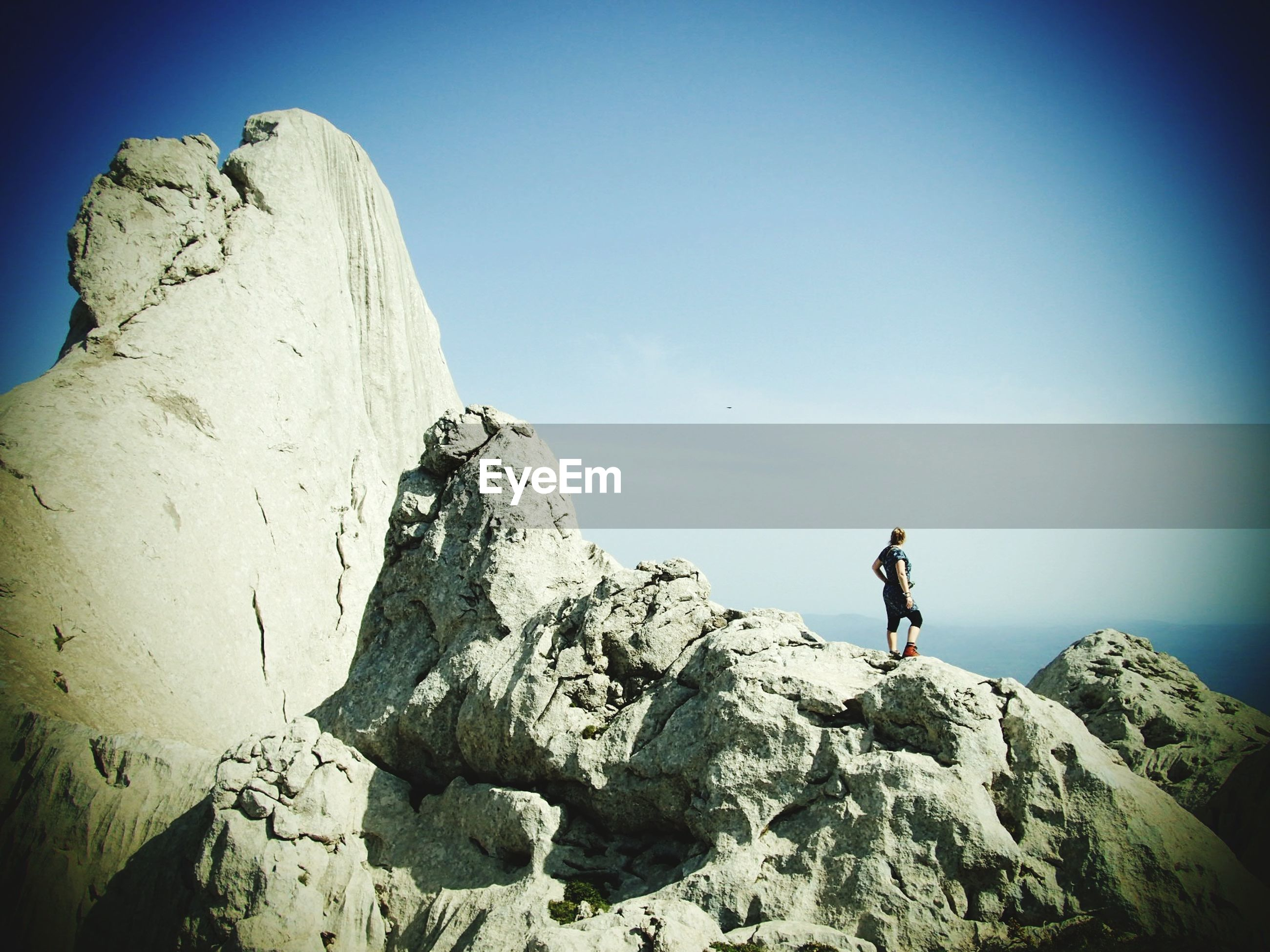 Rear view of woman standing on rock formation against sky