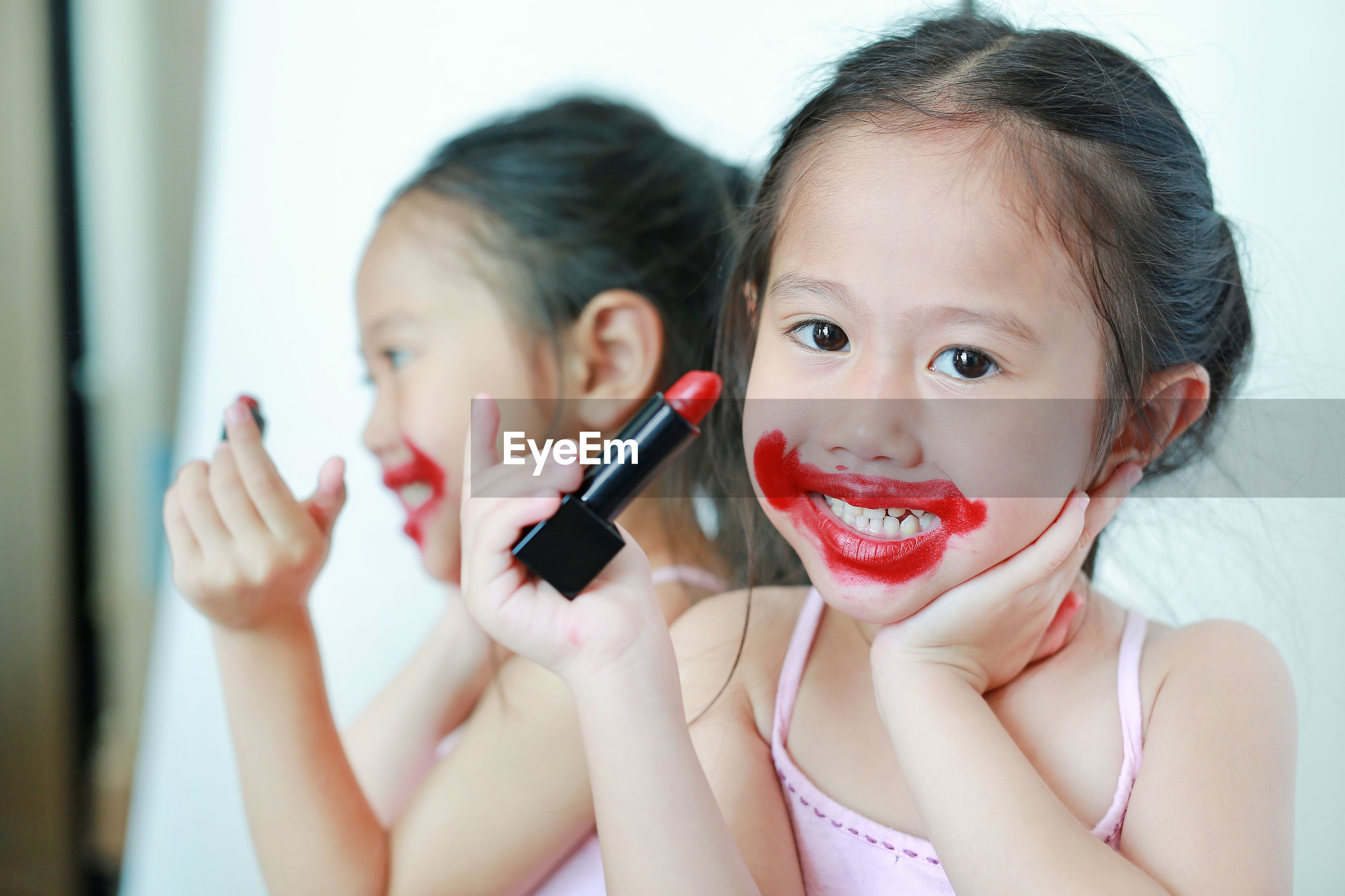 Portrait of cute mischievous girl holding red lipstick at home