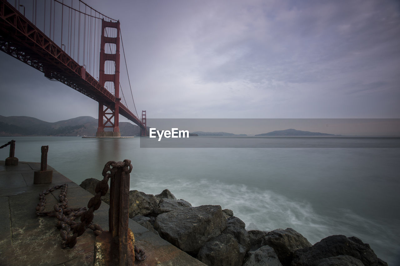 water, sky, sea, rock, built structure, cloud - sky, beauty in nature, solid, nature, bridge, scenics - nature, architecture, rock - object, bridge - man made structure, no people, connection, bay, suspension bridge, outdoors