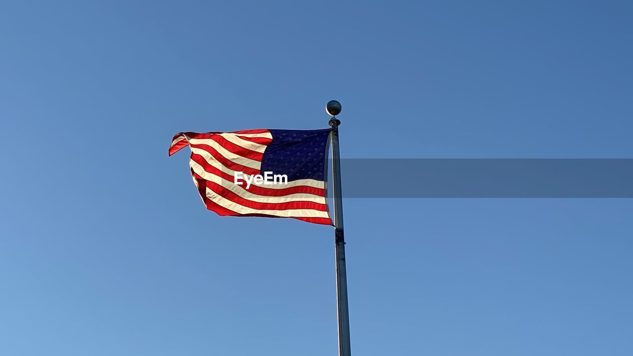 LOW ANGLE VIEW OF FLAGS FLAG AGAINST CLEAR BLUE SKY