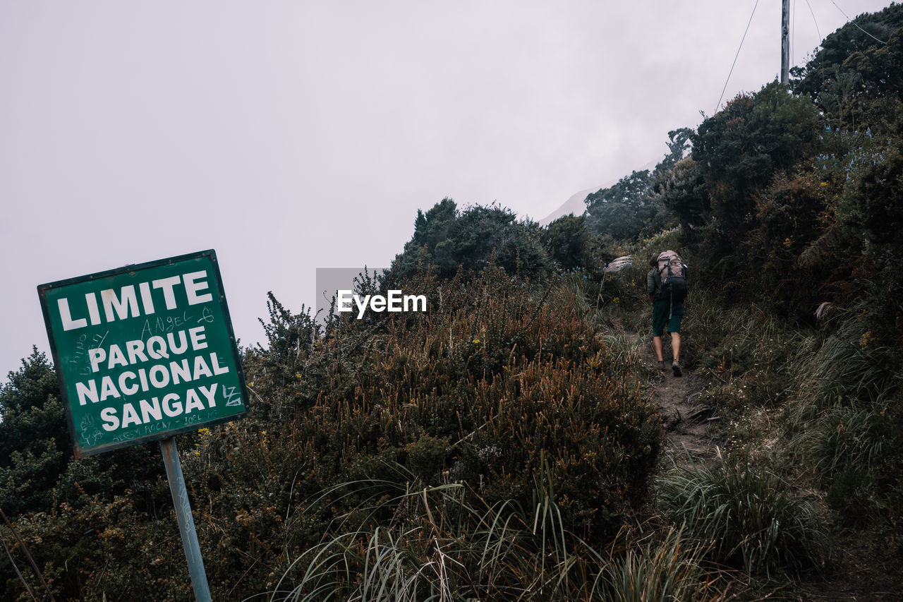sky, plant, nature, communication, real people, text, sign, mountain, men, hiking, leisure activity, beauty in nature, information, activity, grass, land, tranquility, people, non-urban scene, lifestyles, outdoors