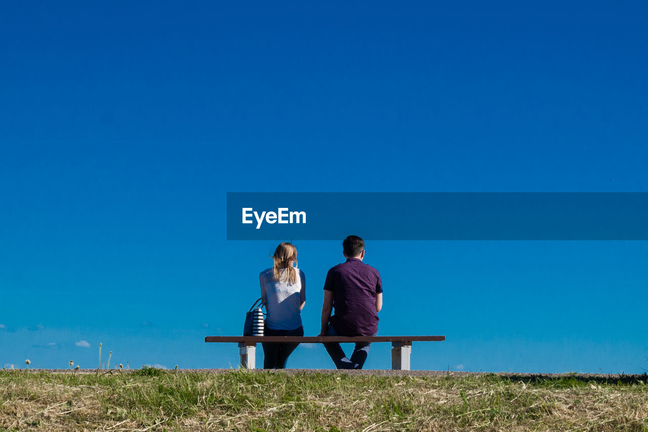 Couple Sitting On Bench Against Clear Blue Sky