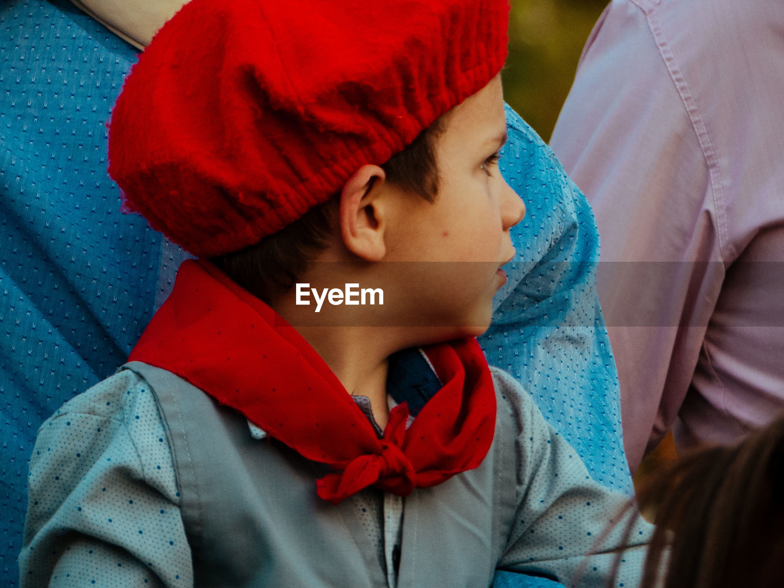Close-up of boy wearing red hat looking away while sitting with parents