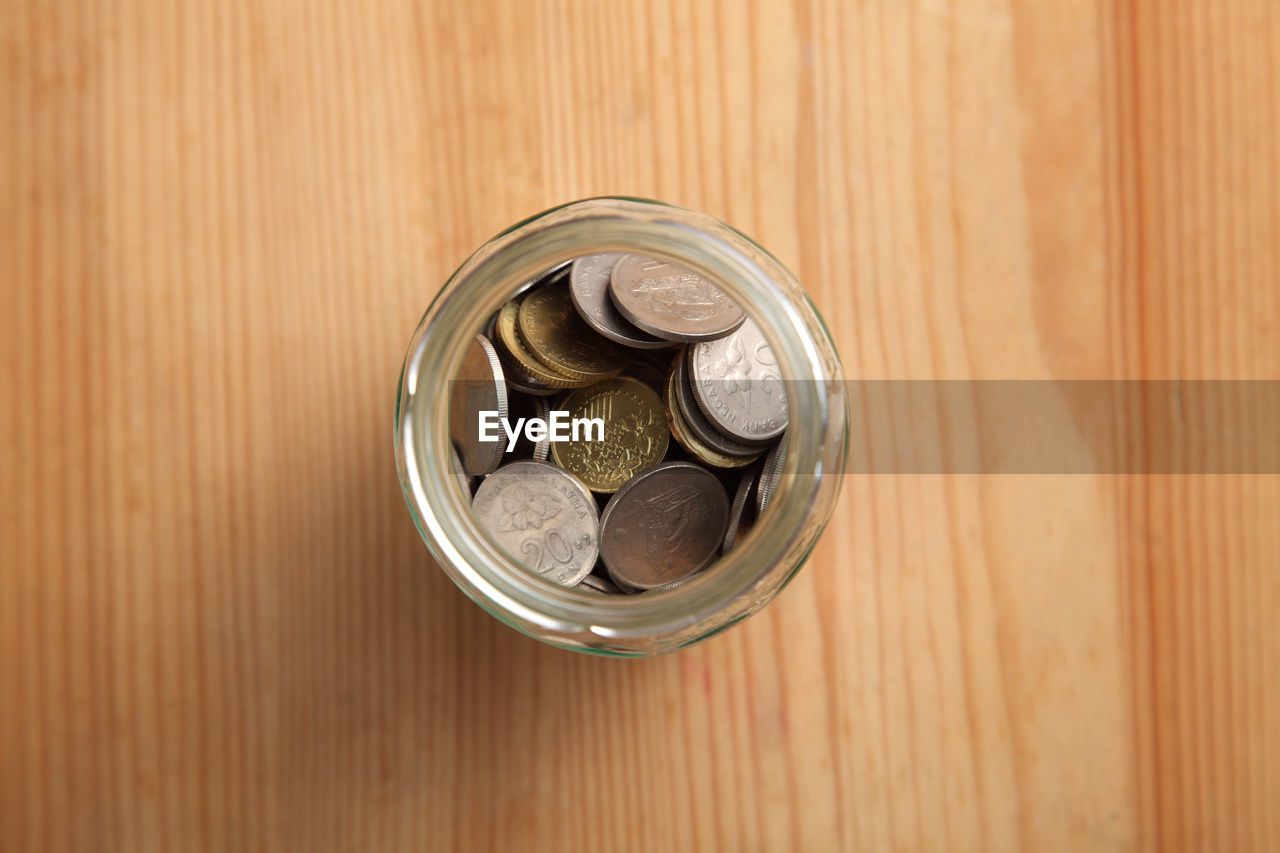 High angle view of coins in glass jar on table
