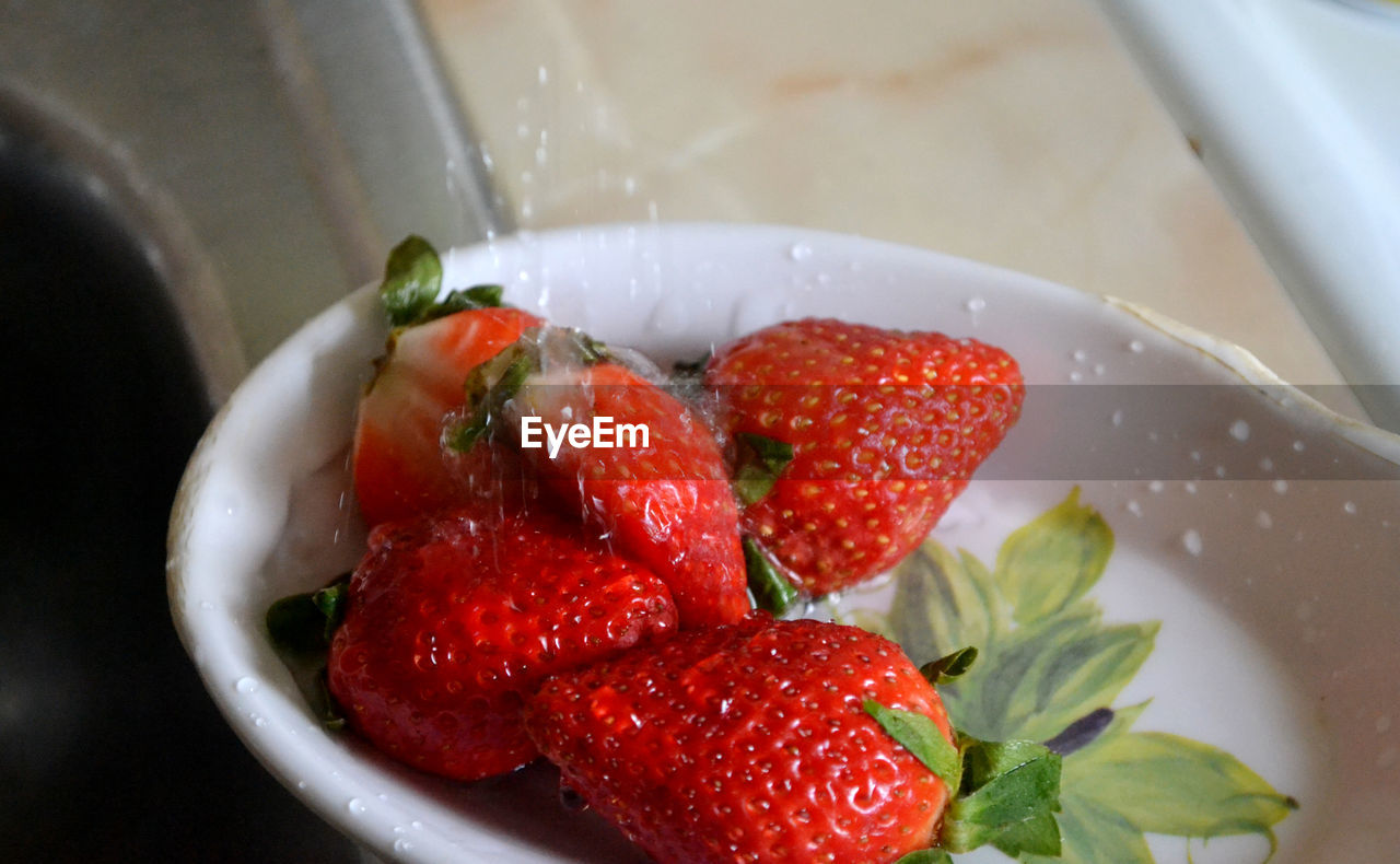Close-up of strawberries being washed in container