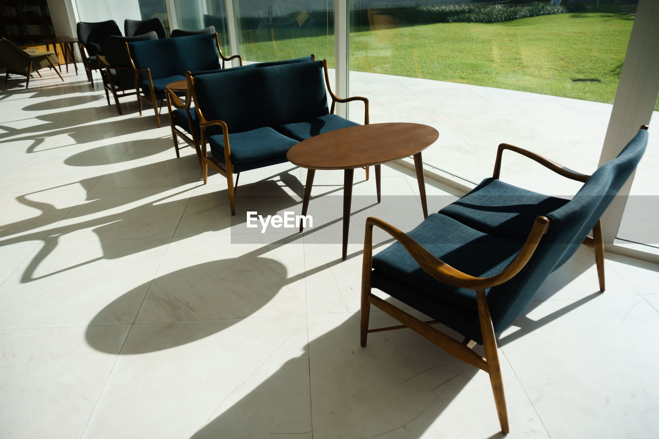 Empty chairs and table against tiled floor