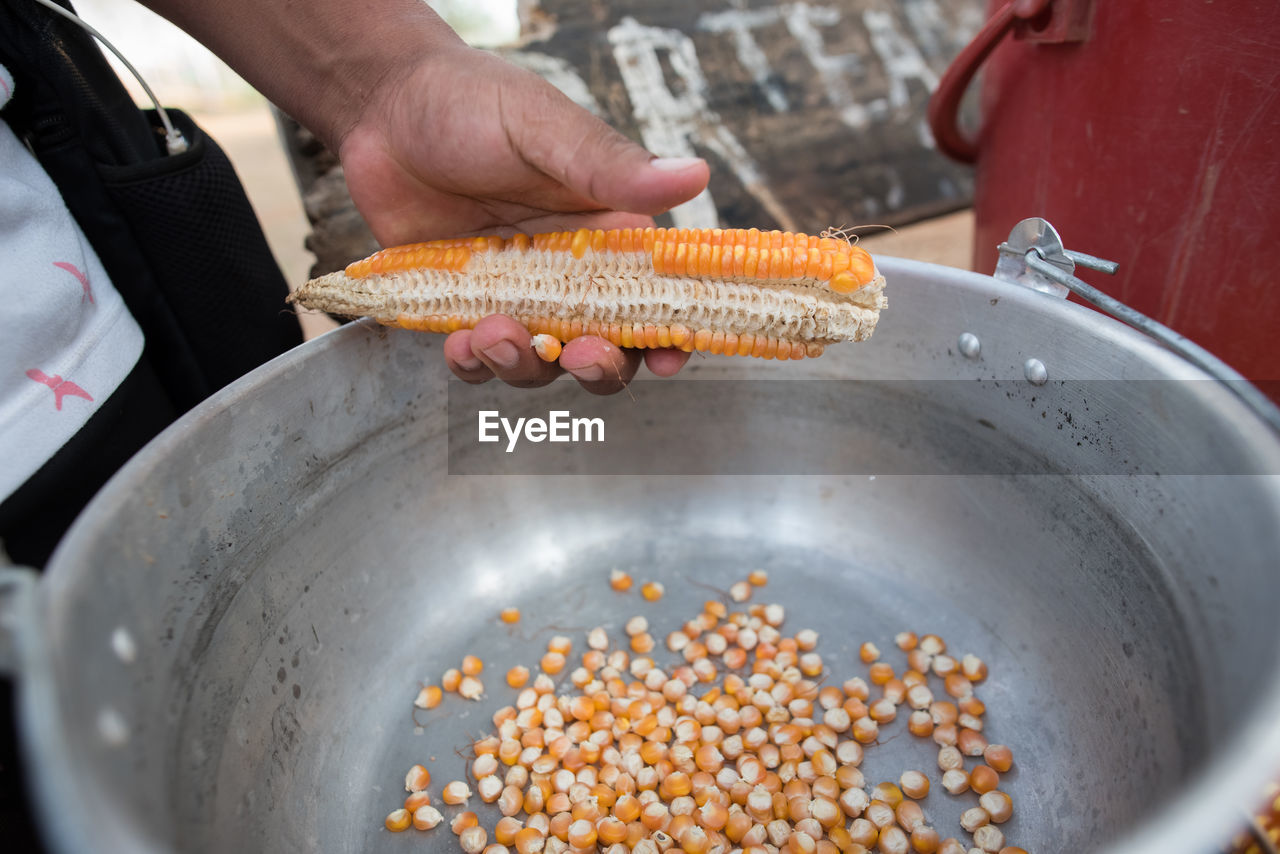 human hand, hand, food, food and drink, human body part, holding, one person, real people, preparation, freshness, indoors, unrecognizable person, healthy eating, corn, wellbeing, high angle view, finger, men, human finger, preparing food, sweetcorn