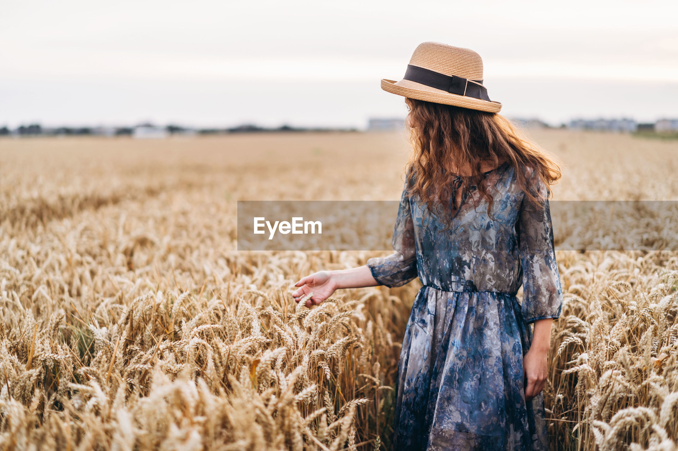 Woman wearing hat standing amidst crops in farm