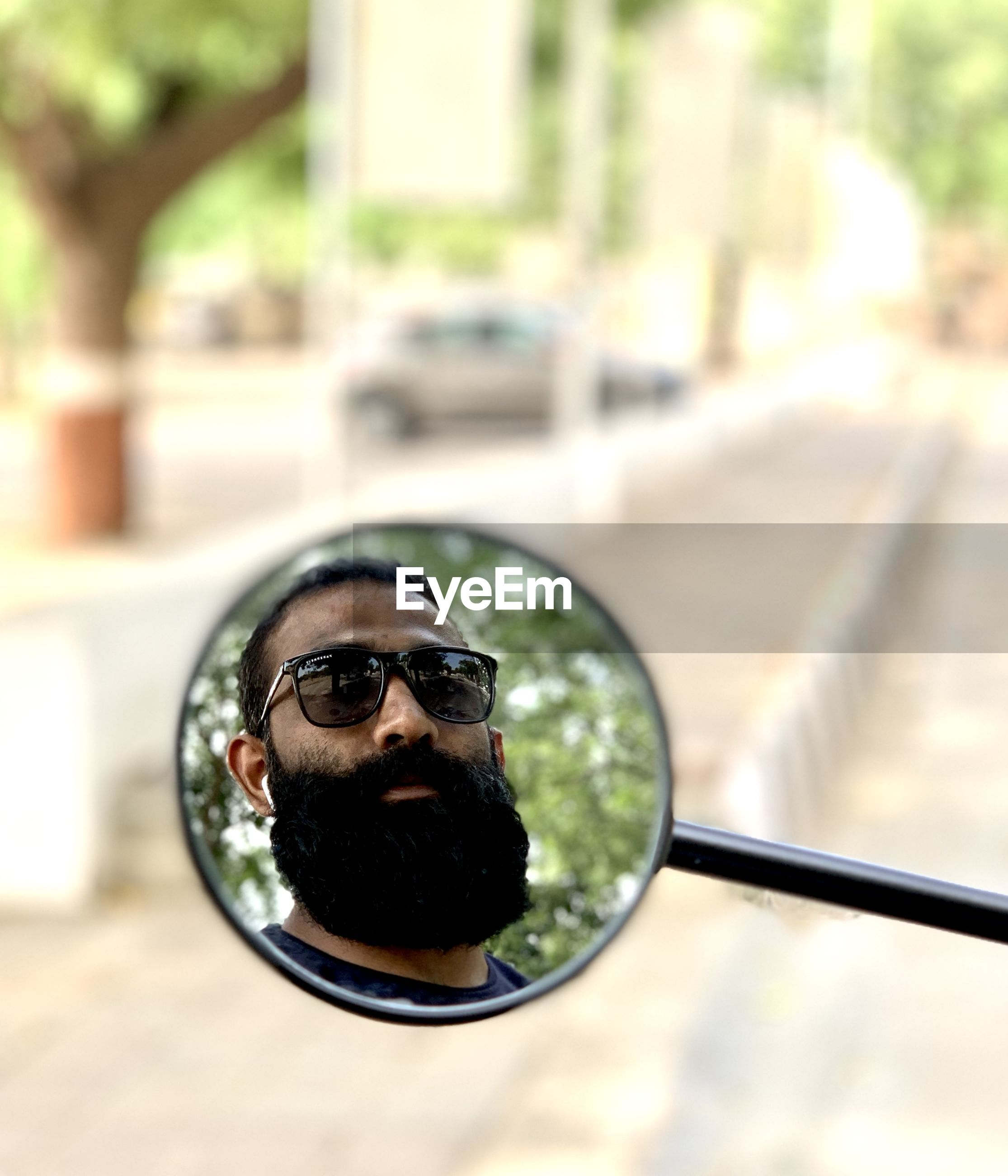 Reflection of man on bike mirror