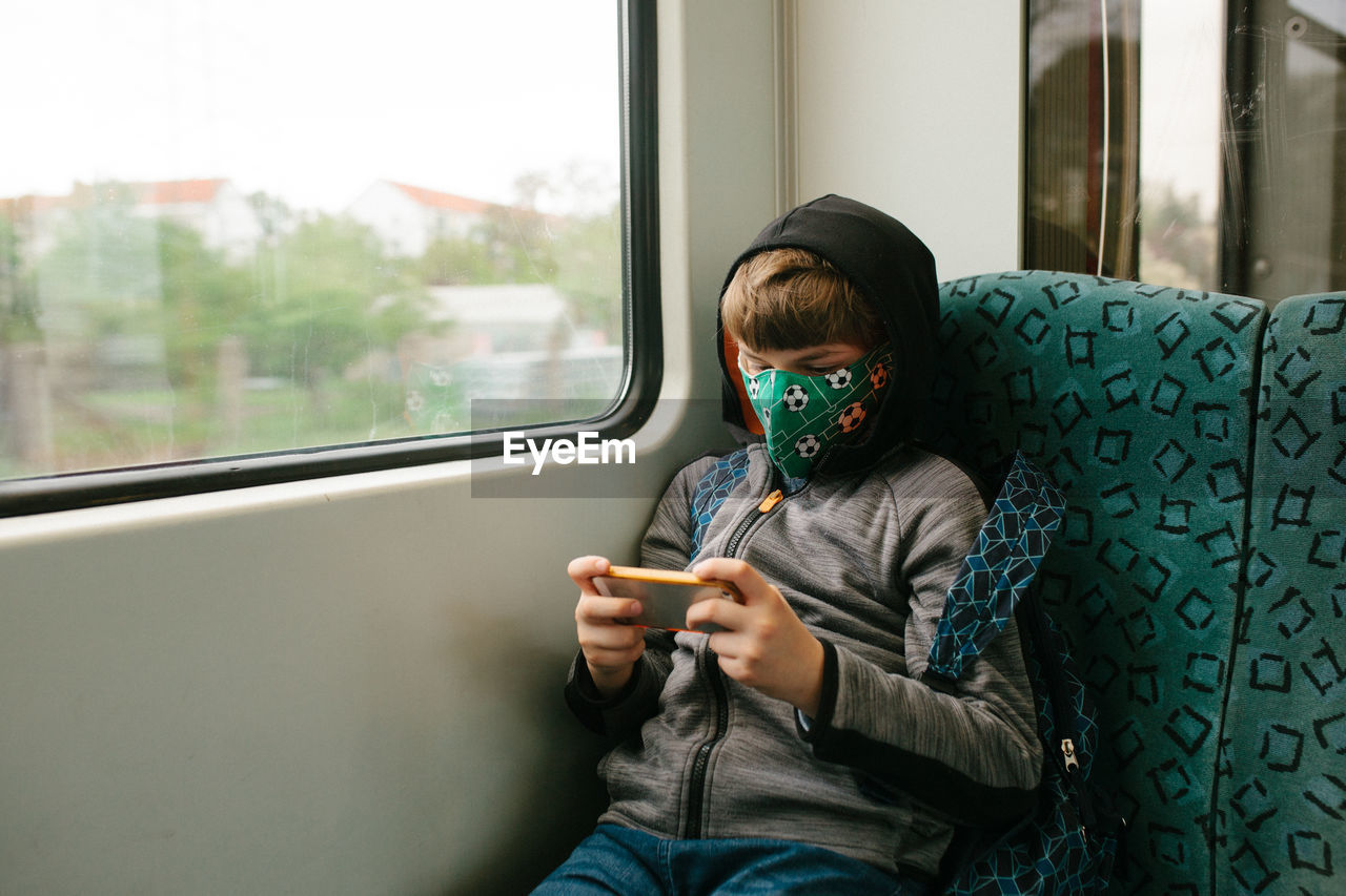Boy wearing mask while using phone during journey