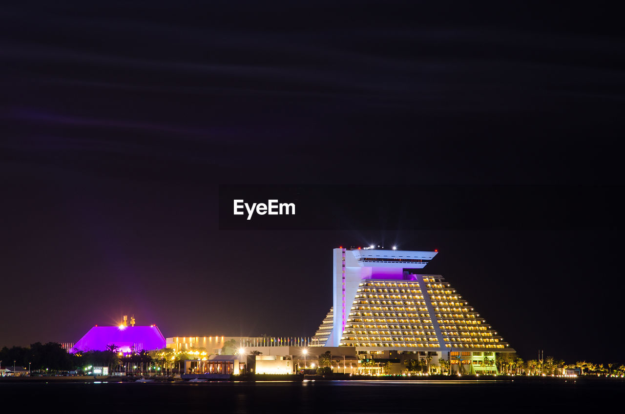 illuminated, night, architecture, building exterior, built structure, sky, building, city, no people, waterfront, travel destinations, nature, skyscraper, office building exterior, water, copy space, modern, urban skyline, tourism, cityscape, purple, luxury, nightlife, financial district