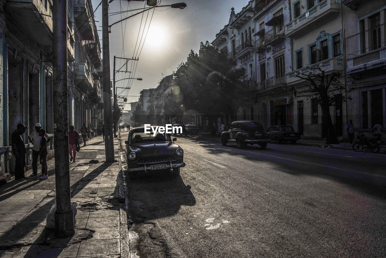 city, building exterior, transportation, mode of transportation, motor vehicle, architecture, street, car, built structure, land vehicle, road, nature, building, sunlight, residential district, city street, sky, city life, the way forward, tree, outdoors