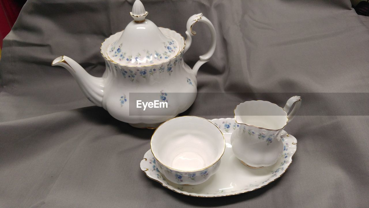 teapot, drink, indoors, crockery, cup, refreshment, white color, food and drink, kitchen utensil, tea, tea - hot drink, hot drink, table, mug, tea cup, no people, high angle view, still life, close-up, ceramics, afternoon tea, tray, non-alcoholic beverage