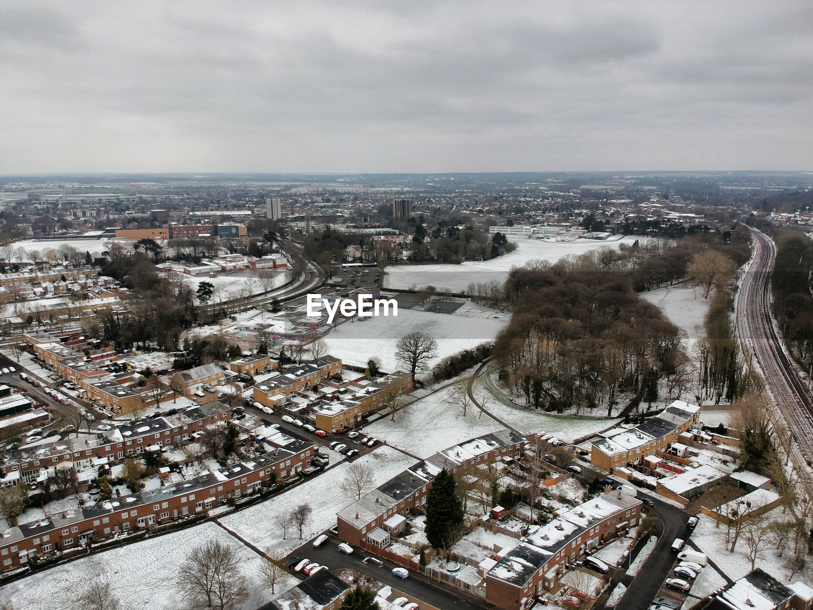 Aerial view of snowy townscape against sky