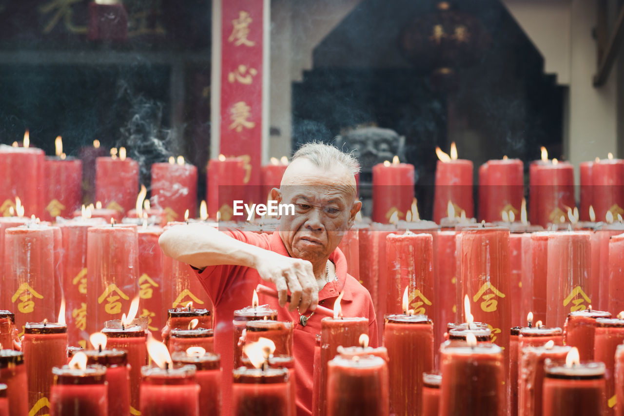 Man Igniting Candle In Temple