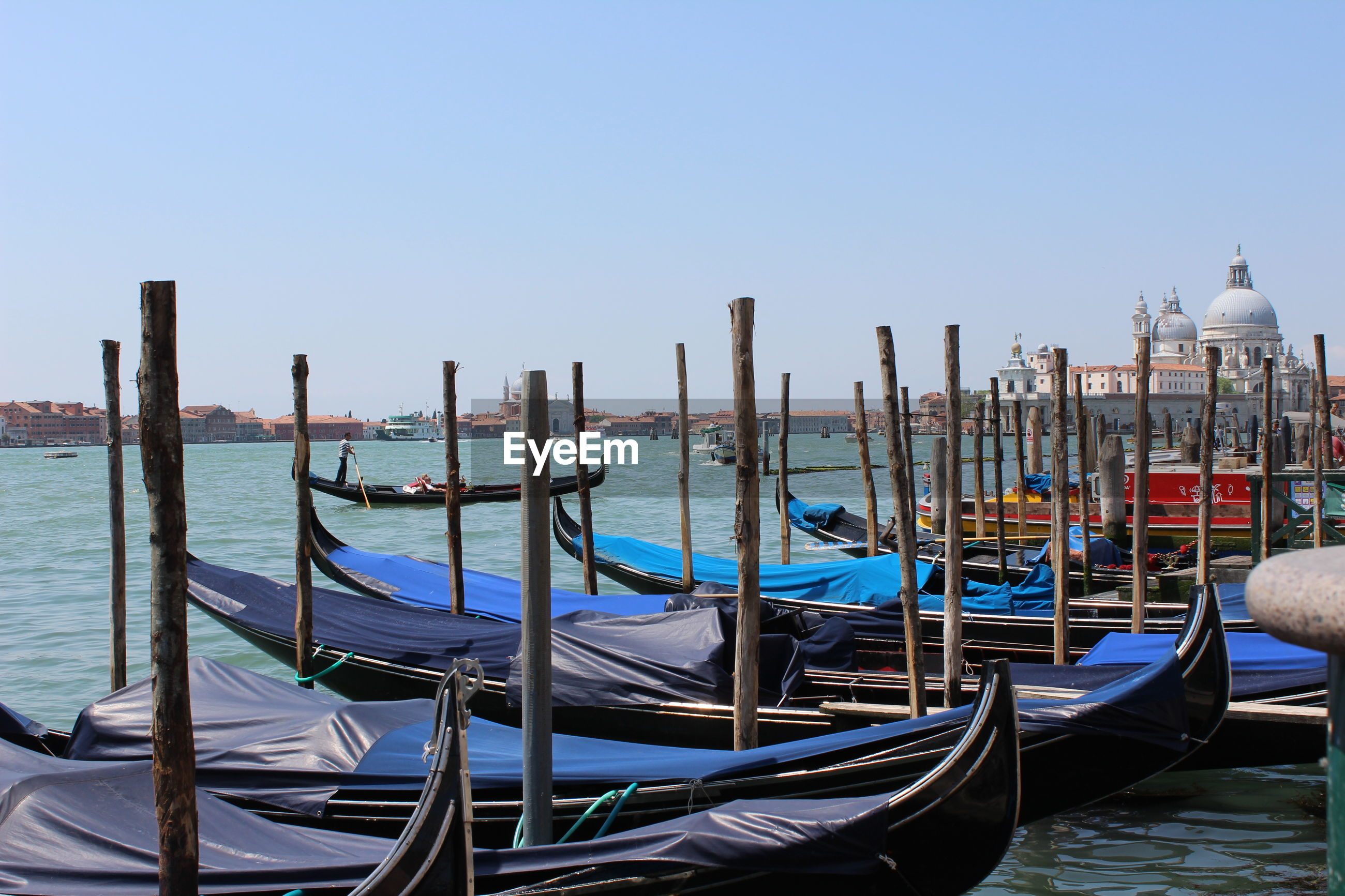 Gondolas moored in grand canal against clear sky