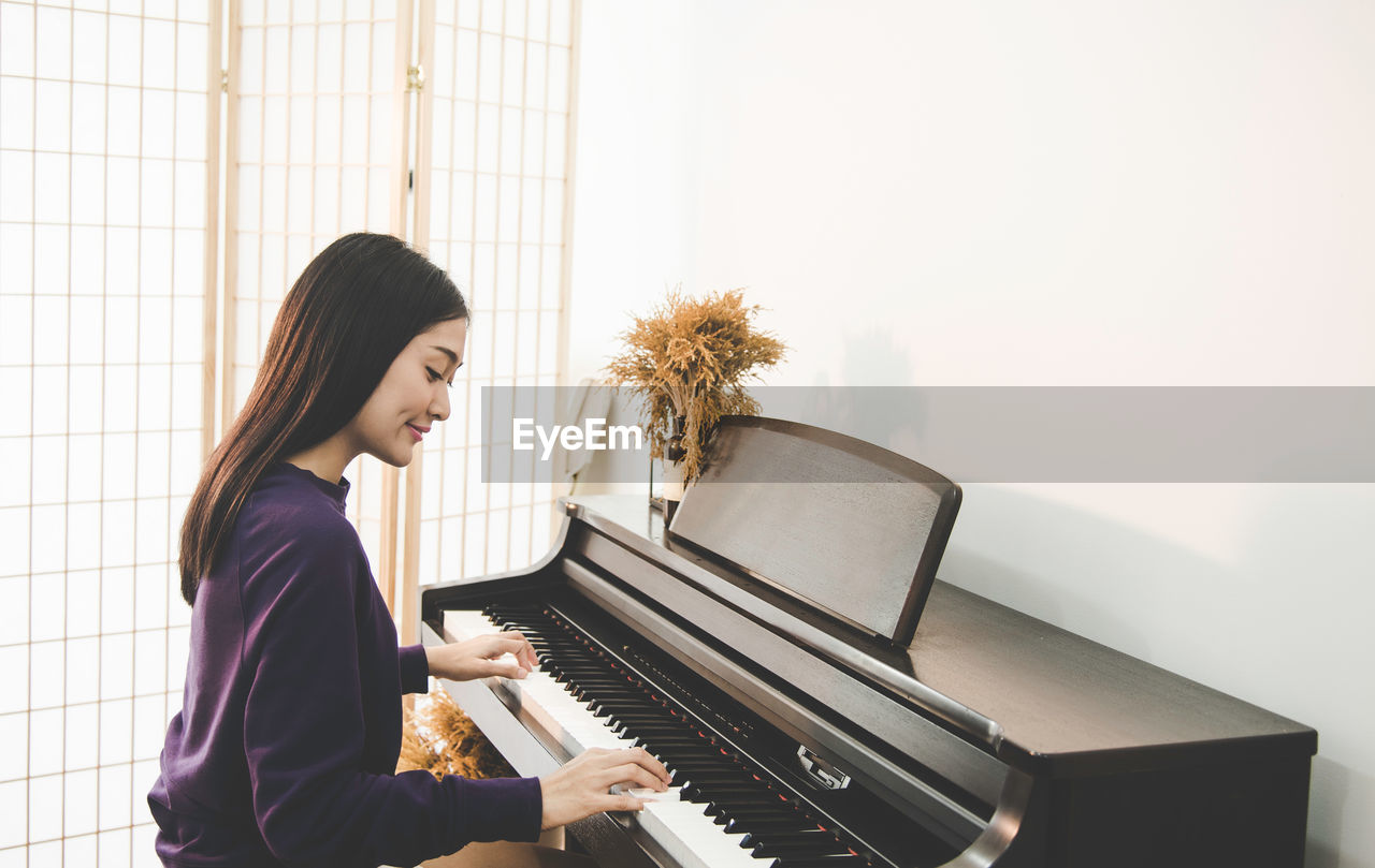 musical equipment, musical instrument, music, piano, arts culture and entertainment, one person, young adult, waist up, young women, side view, indoors, women, sitting, playing, home interior, adult, lifestyles, musician, pianist, skill, hairstyle, piano key, grand piano, keyboard