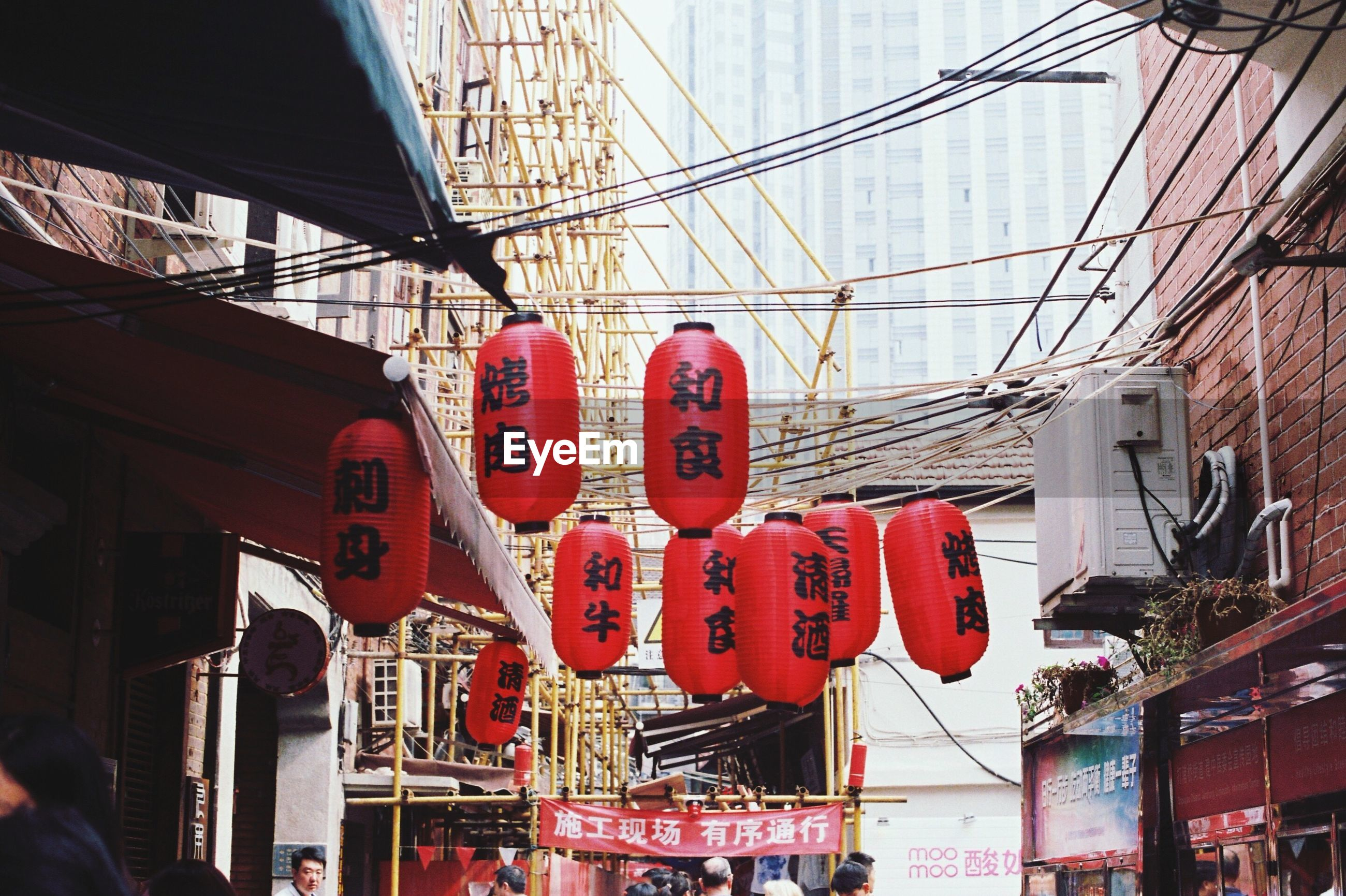 hanging, red, built structure, architecture, building exterior, text, communication, low angle view, city, men, retail, market, cable, indoors, day, western script, shopping, non-western script, store