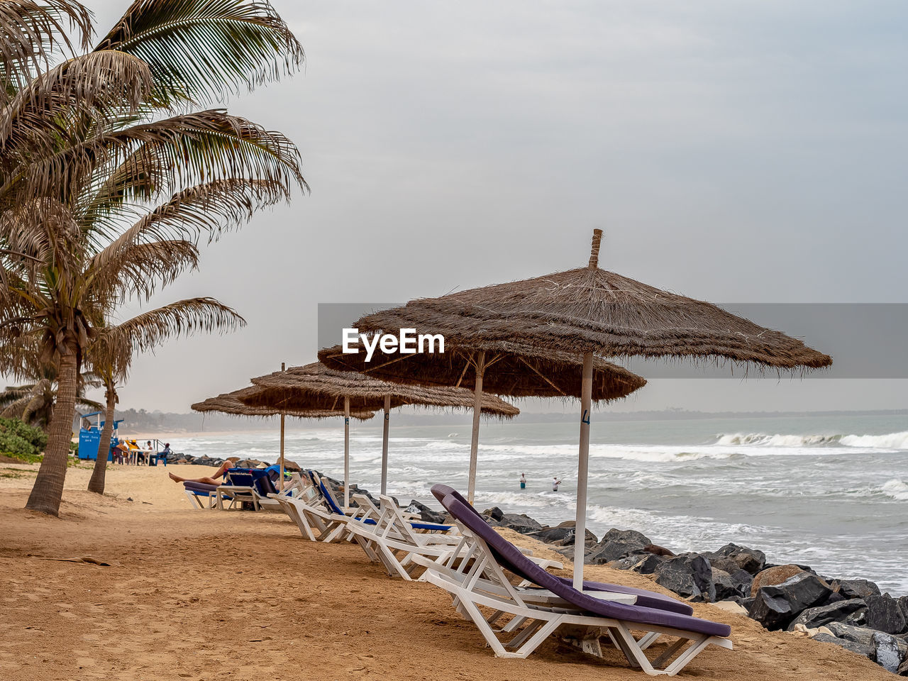 water, sea, beach, land, sky, thatched roof, chair, nature, sand, parasol, beauty in nature, palm tree, tropical climate, lounge chair, day, roof, tranquility, umbrella, tree, horizon over water, outdoors, no people