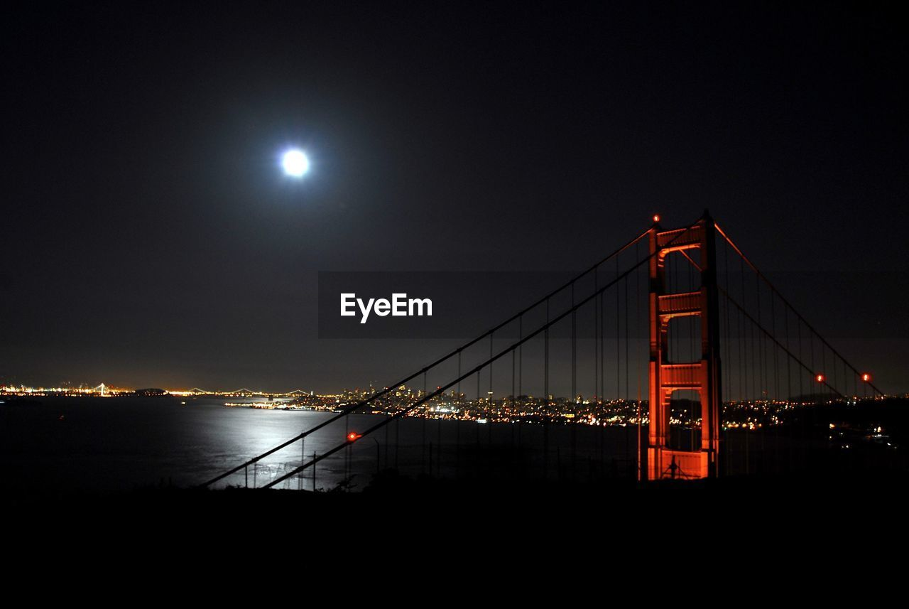 sky, night, built structure, illuminated, architecture, moon, connection, suspension bridge, bridge, full moon, water, bridge - man made structure, transportation, nature, engineering, travel destinations, outdoors, beauty in nature, moonlight, bay