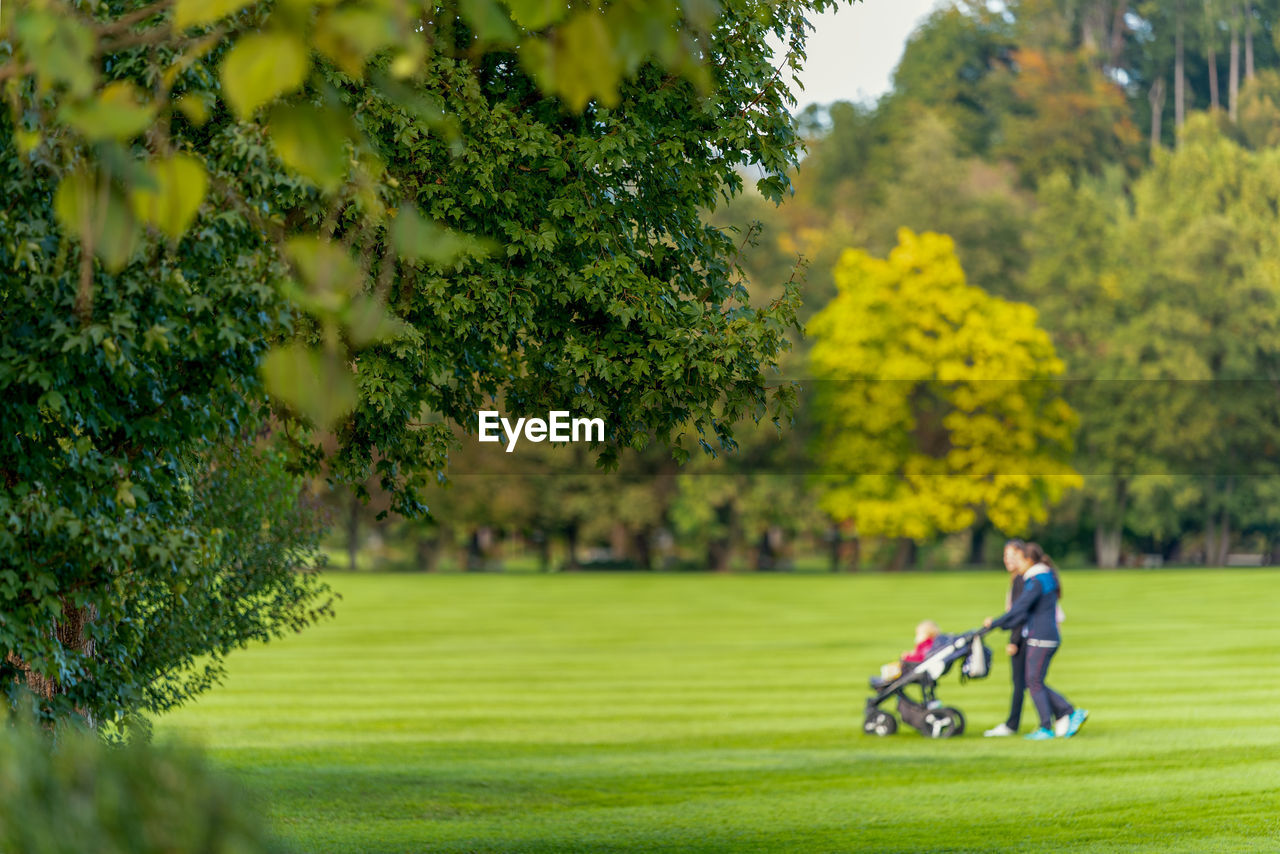 Full length of man and woman with baby stroller on golf course