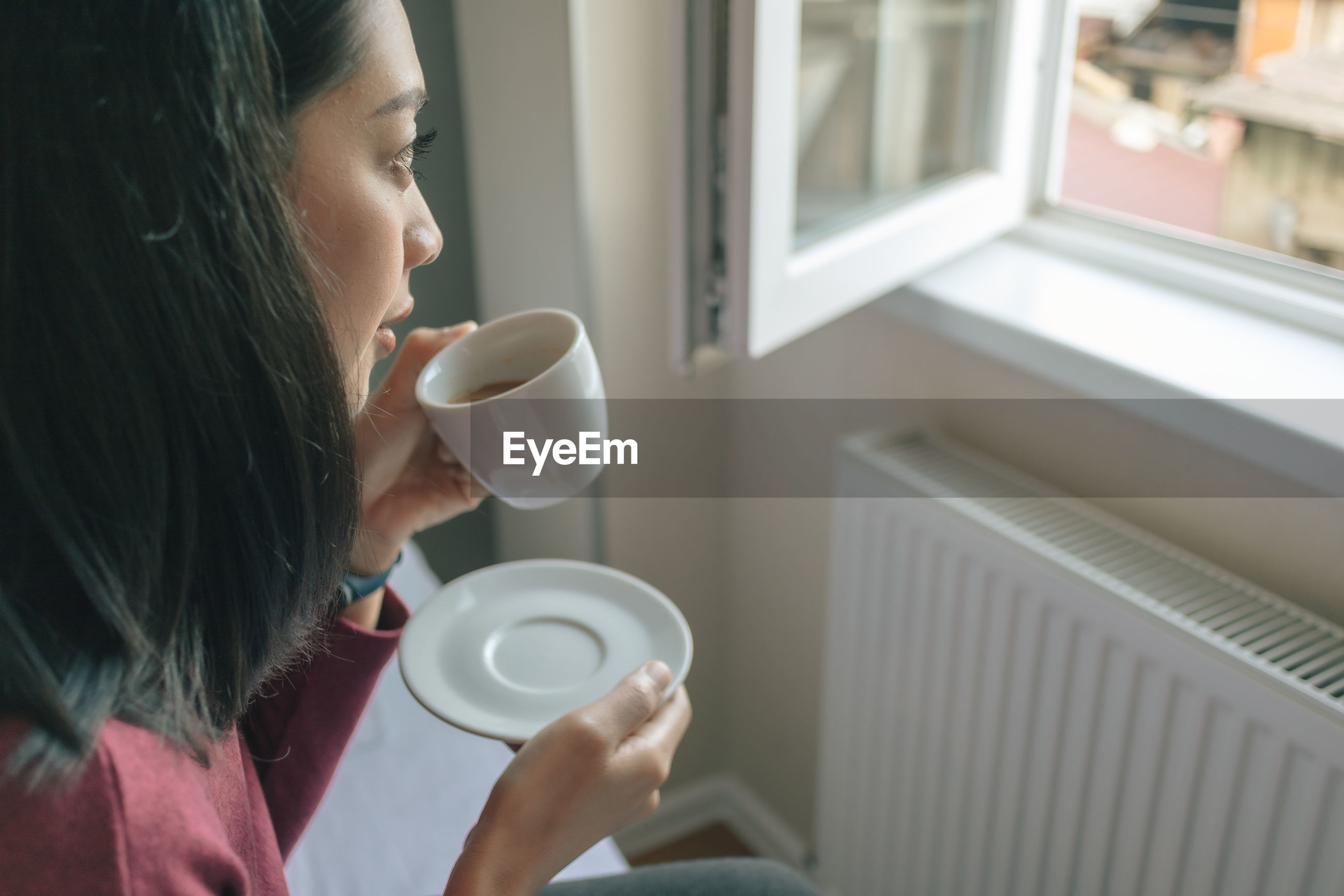 Woman holding coffee cup while sitting by window