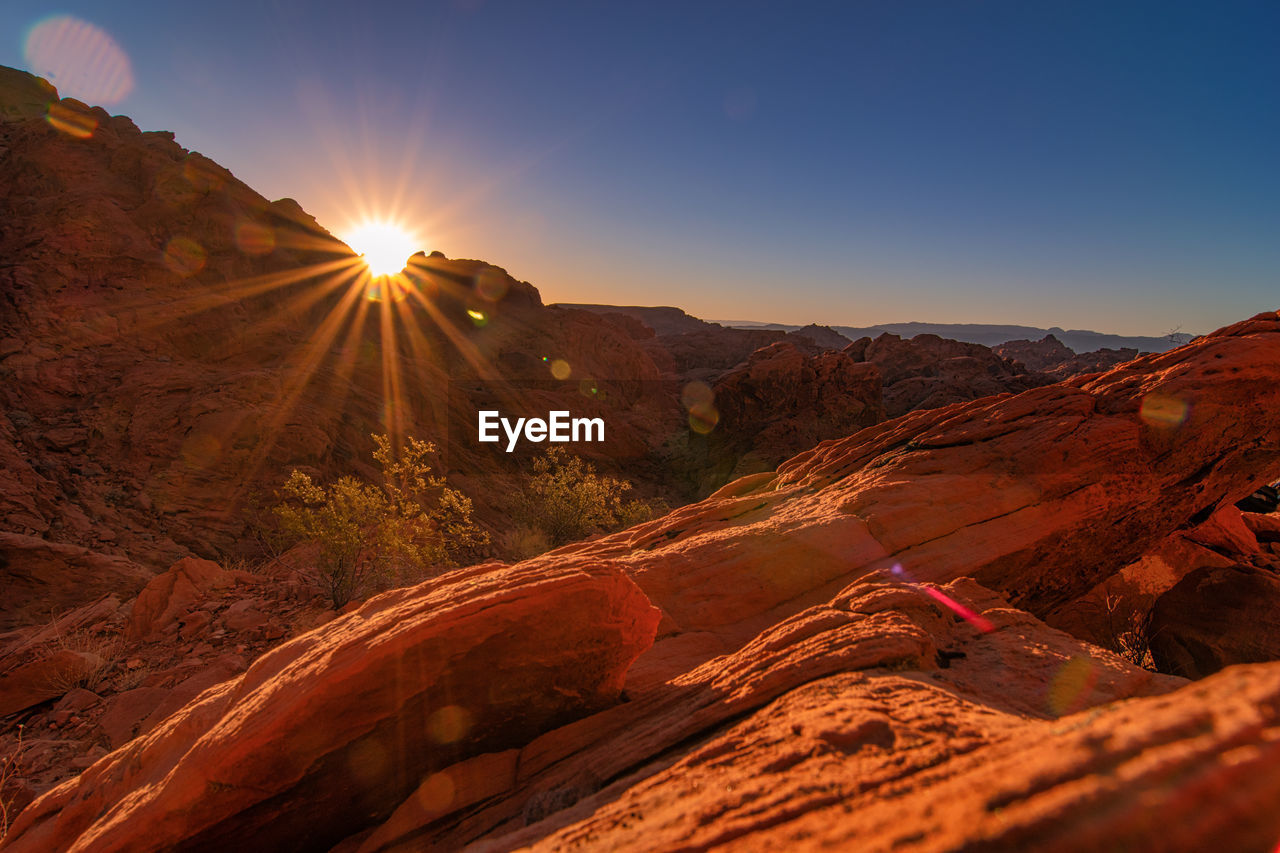 sky, scenics - nature, mountain, beauty in nature, tranquil scene, tranquility, sunlight, non-urban scene, environment, nature, landscape, sunbeam, sun, lens flare, mountain range, no people, idyllic, sunset, physical geography, remote, outdoors, arid climate, climate