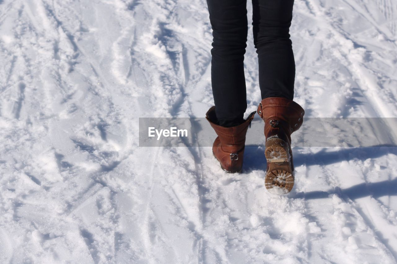 snow, one person, low section, real people, human body part, body part, winter, cold temperature, human leg, nature, day, white color, lifestyles, outdoors, leisure activity, high angle view, standing, shoe, warm clothing, human foot, human limb