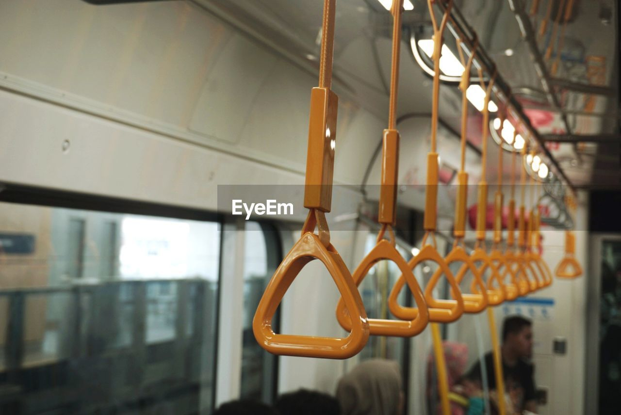 Close-up of yellow handles hanging in train