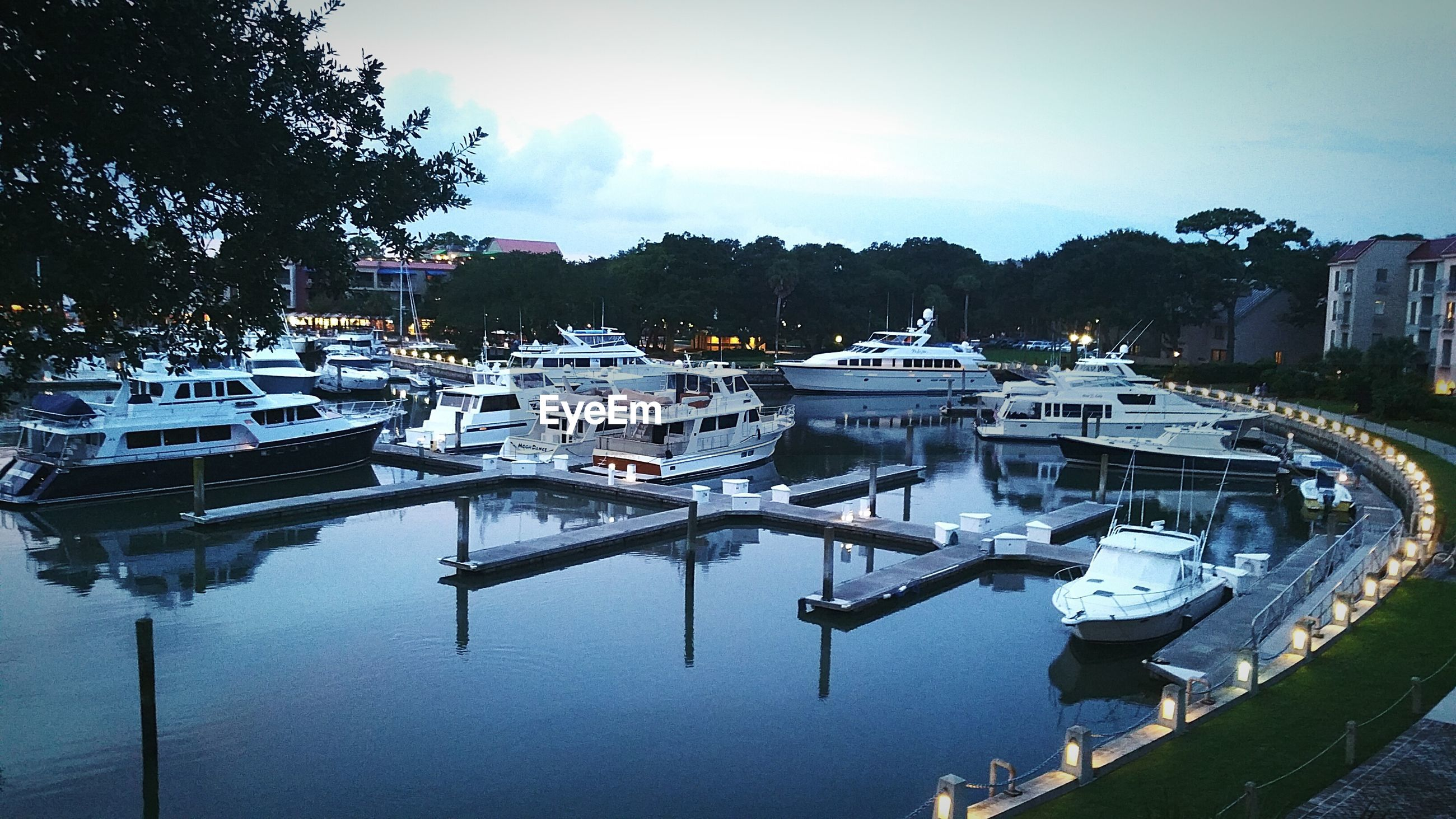 Boats moored on harbor against sky at dusk