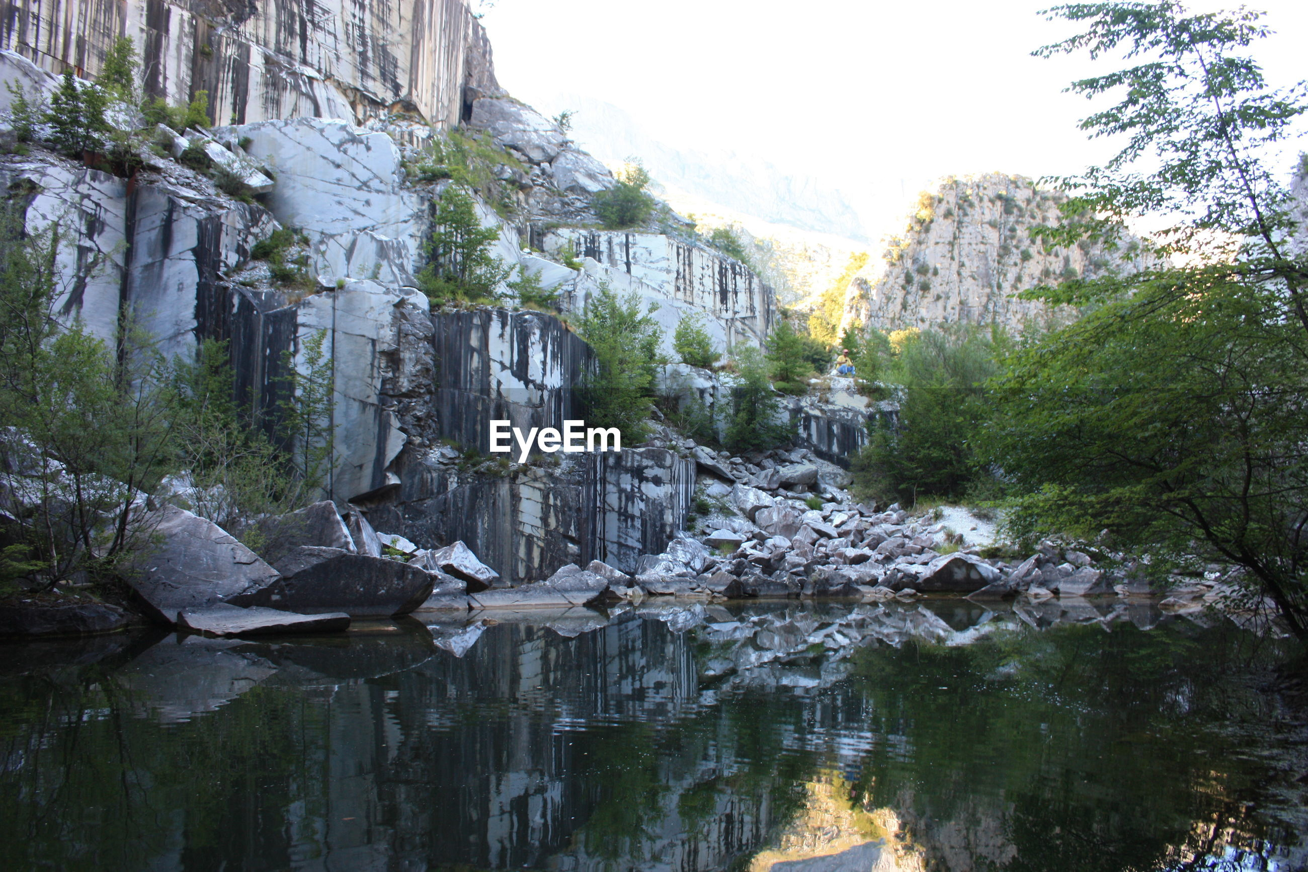 Small natural lake inside a marble quarry in mountain in apuan alps