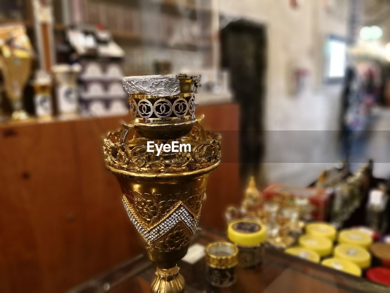 Close-Up Of Golden Perfume Bottle On Table