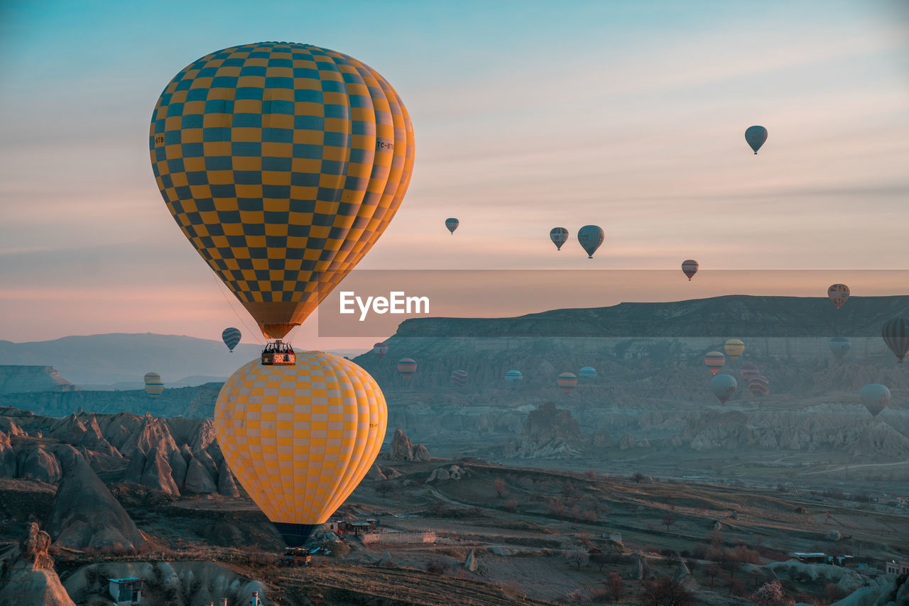 hot air balloon, ballooning festival, transportation, mid-air, flying, adventure, nature, rock - object, mountain, travel, beauty in nature, air vehicle, sky, outdoors, multi colored, sunset, scenics, no people, day, rock hoodoo