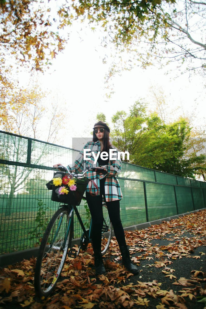 Full length of woman with bicycle by fence against sky