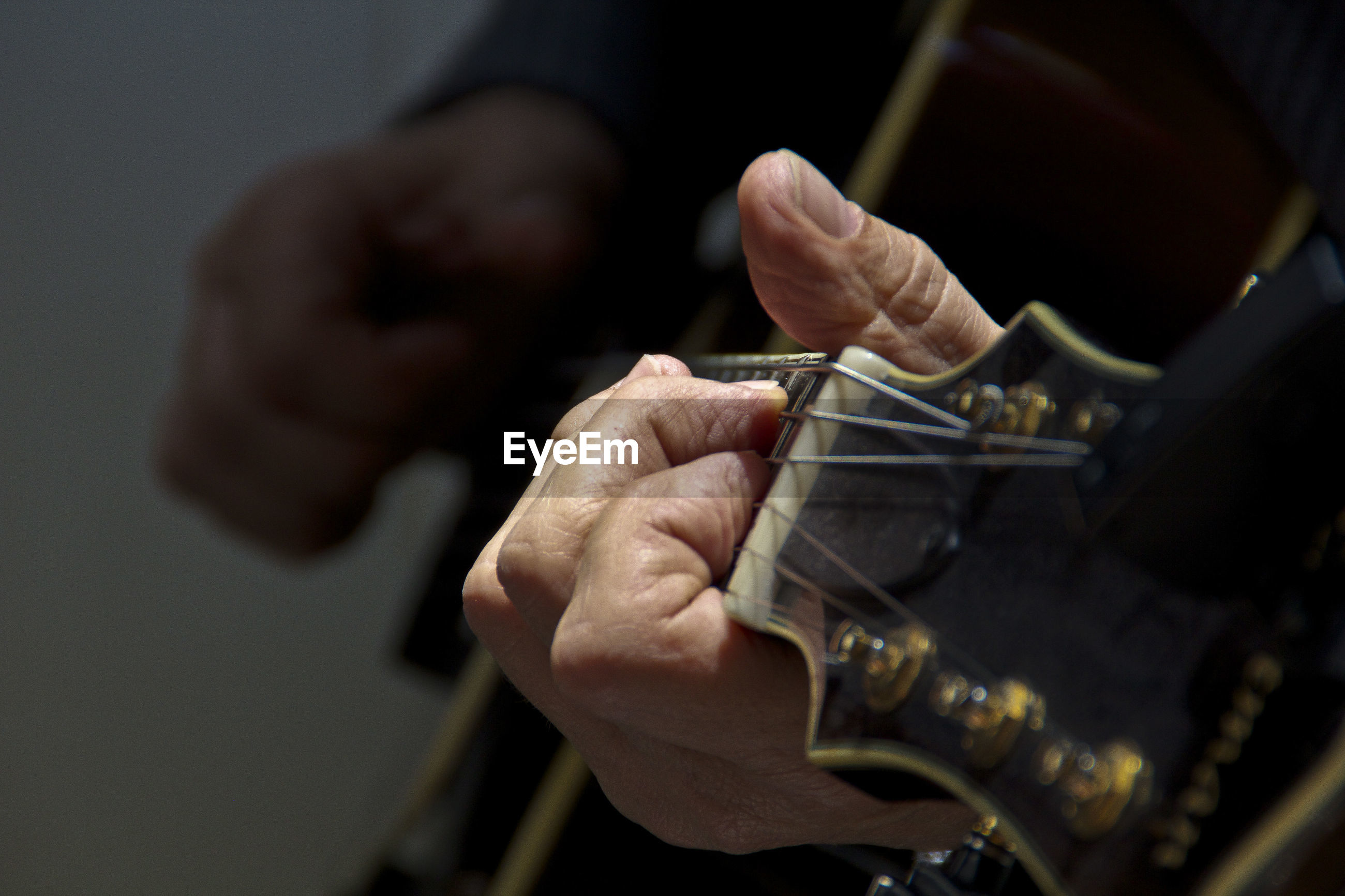 Midsection of guitarist playing guitar