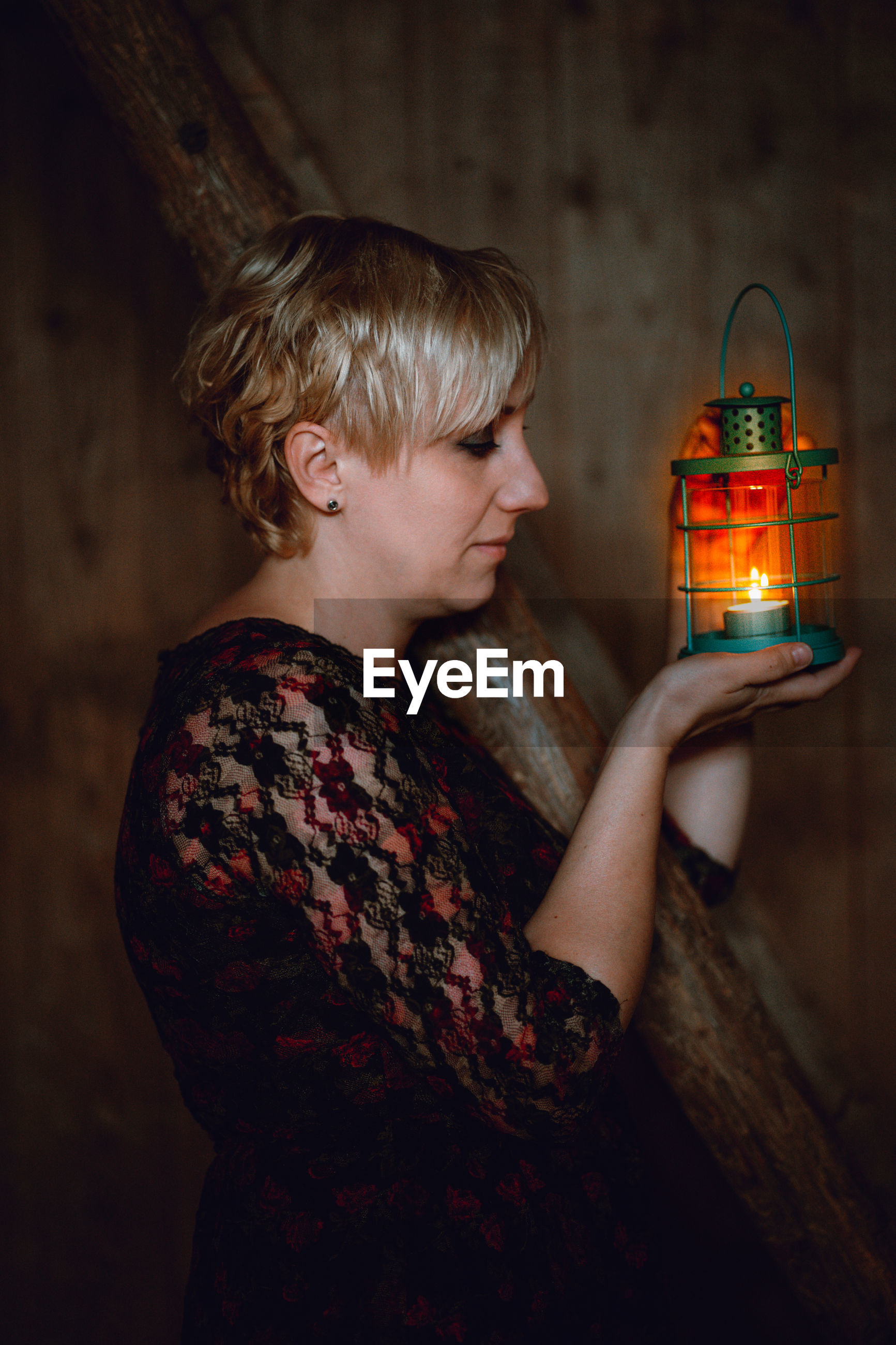 Side view of woman holding illuminated candle