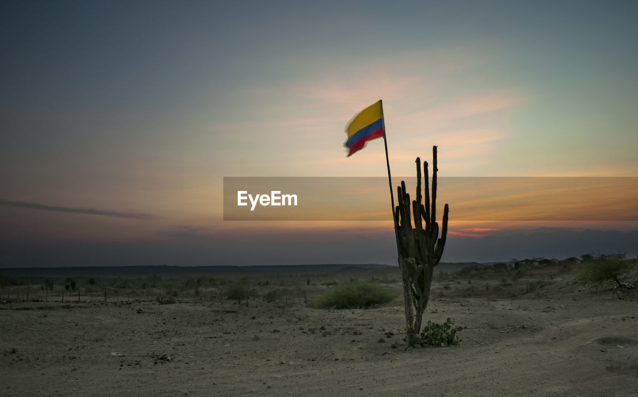 Colombian flag on field against sky at sunset