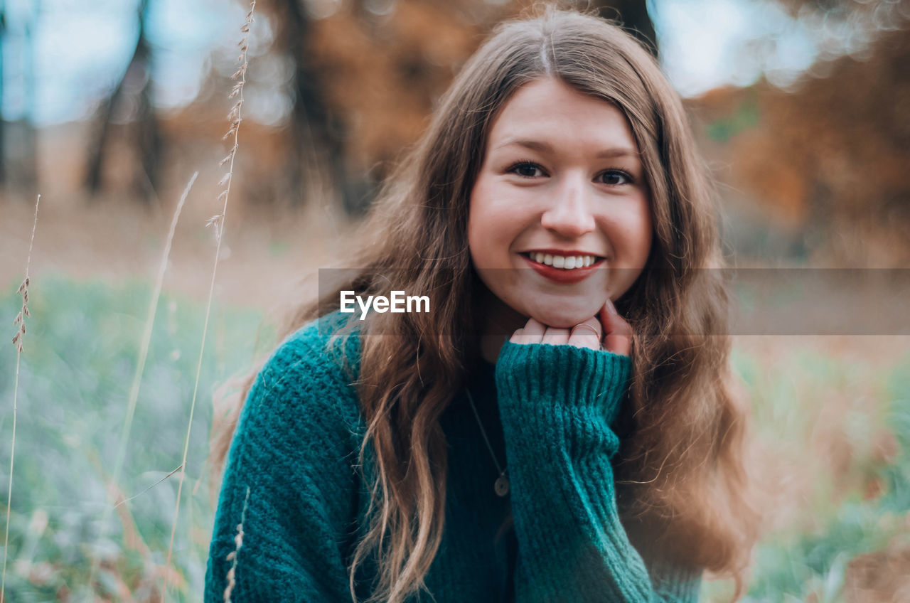 Portrait of smiling girl sitting on field