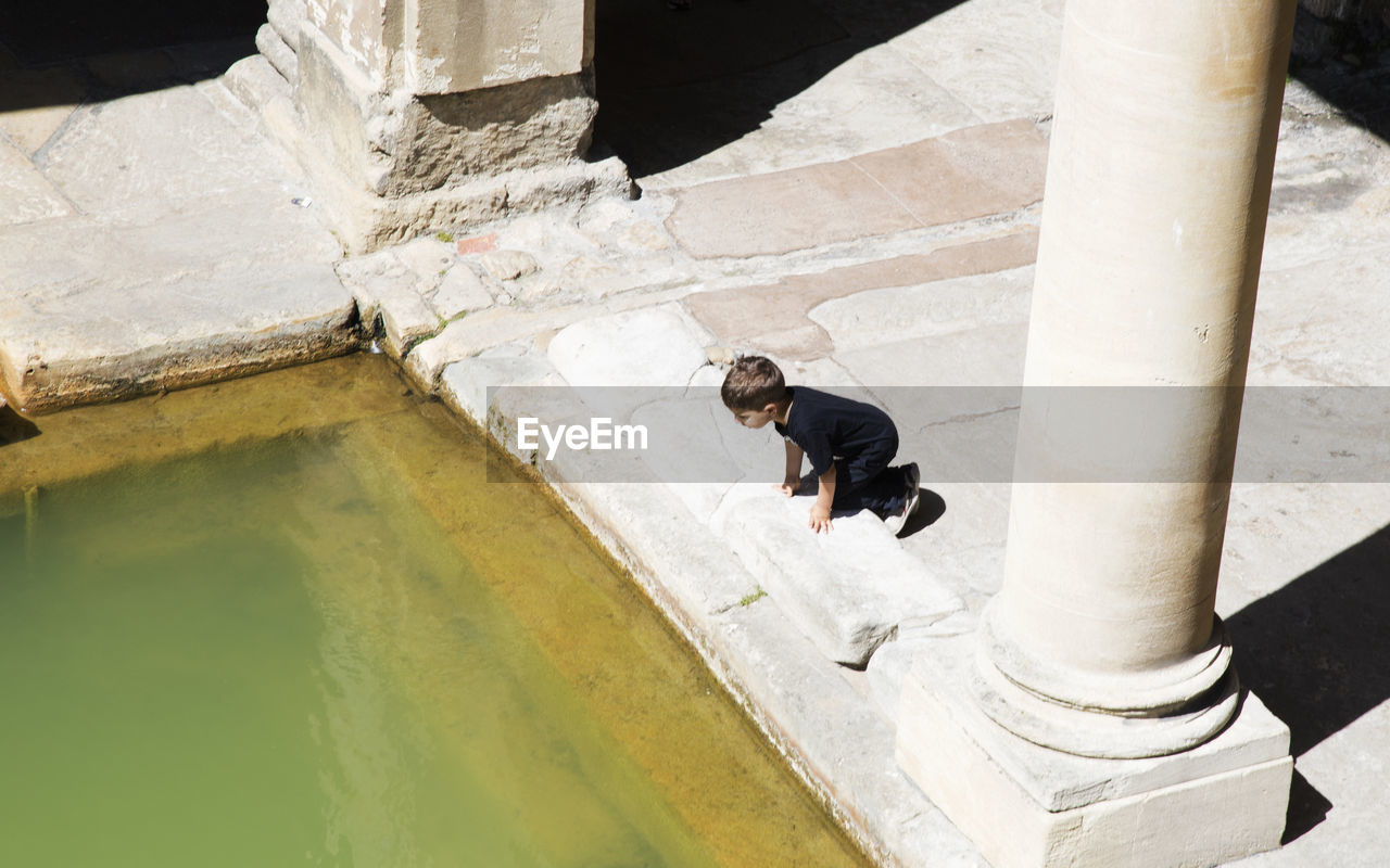 one person, architecture, real people, water, full length, day, nature, men, lifestyles, built structure, leisure activity, outdoors, sunlight, young adult, high angle view, casual clothing, young men, staircase, architectural column