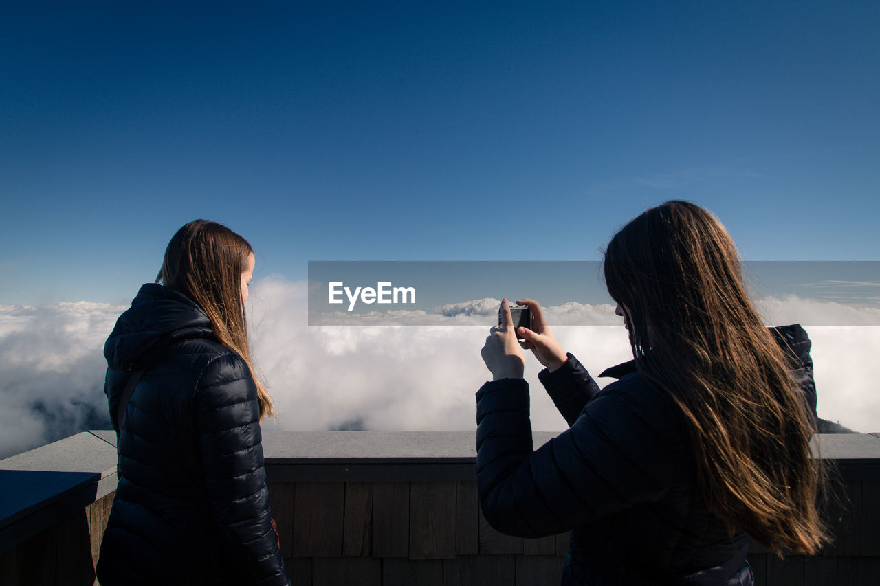 Woman photographing friend at observation point against blue sky