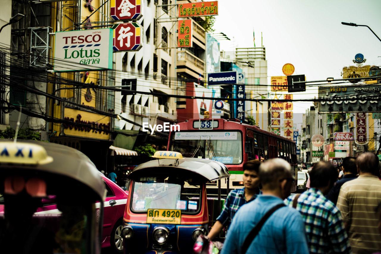 People Walking By Vehicles On Street Amidst Buildings In City