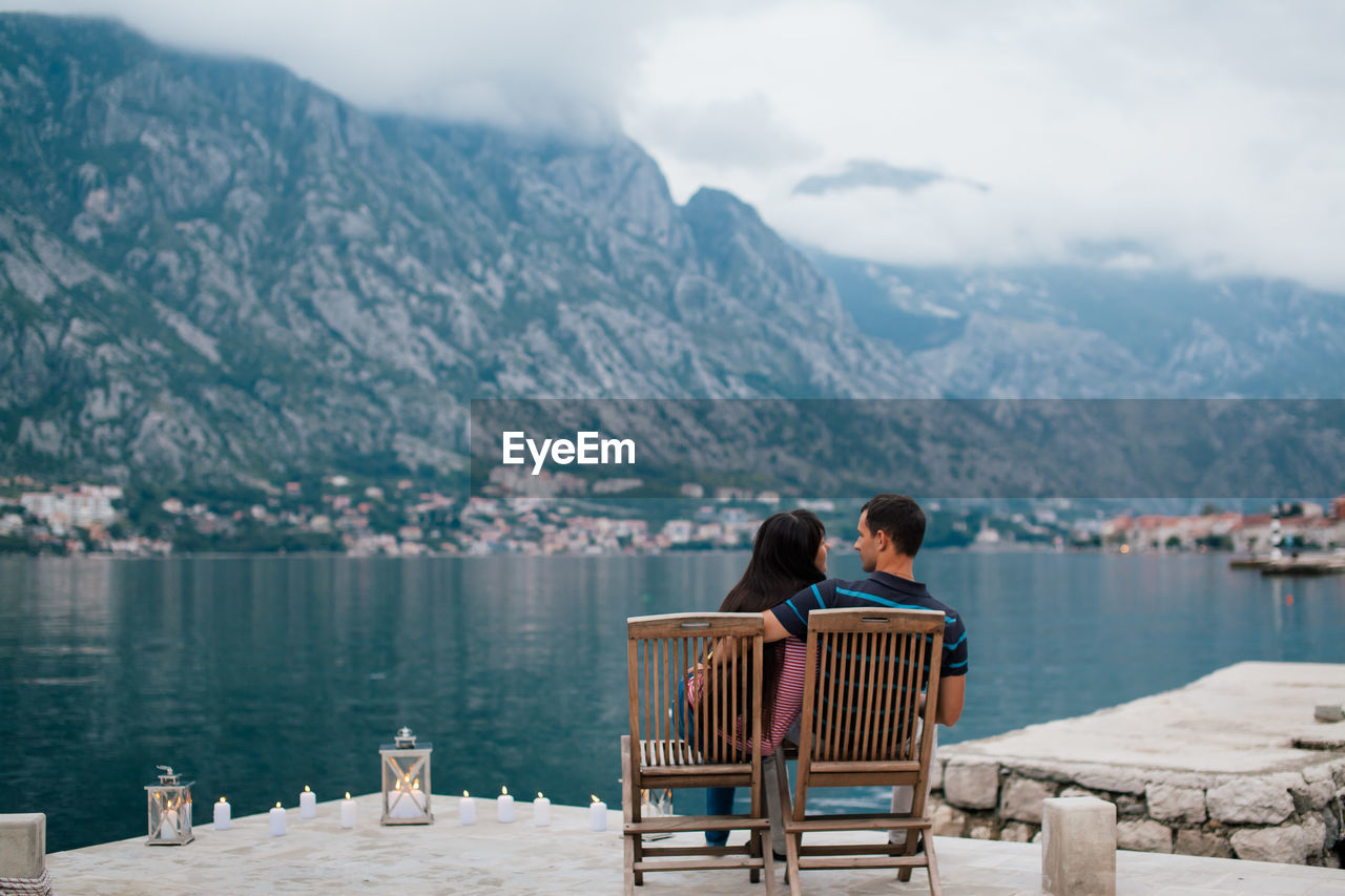 Rear view of couple sitting on lakeshore against mountains