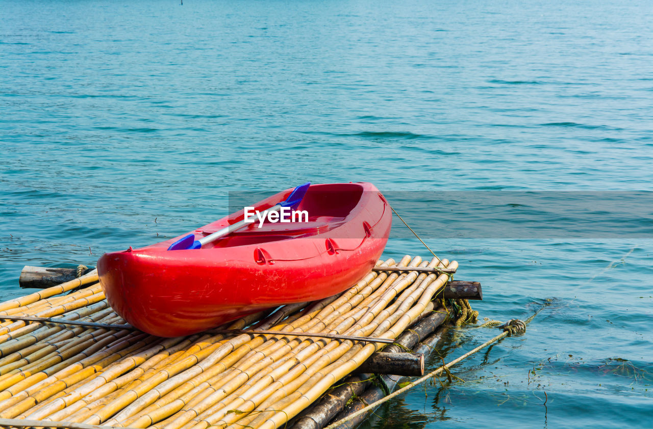 water, nautical vessel, transportation, no people, lake, nature, day, red, mode of transportation, wood - material, blue, moored, outdoors, tranquility, tranquil scene, pier, buoy, high angle view, floating on water, inflatable