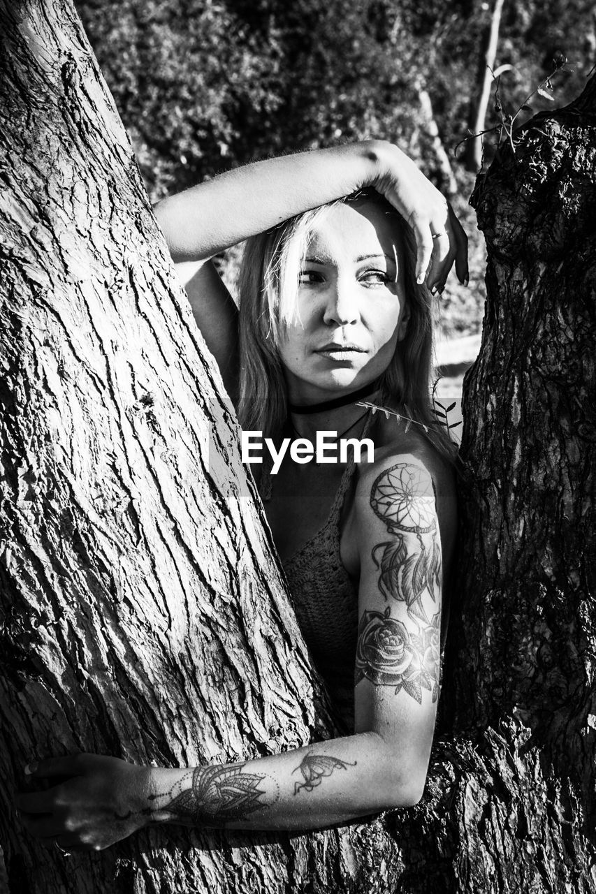 Side View Of Thoughtful Woman With Tattoos On Hand Standing By Tree Trunk