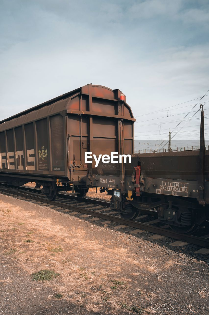 transportation, train, mode of transportation, rail transportation, train - vehicle, track, railroad track, land vehicle, sky, freight train, cloud - sky, business, freight transportation, nature, public transportation, day, no people, outdoors, built structure, stationary, shunting yard, railroad car