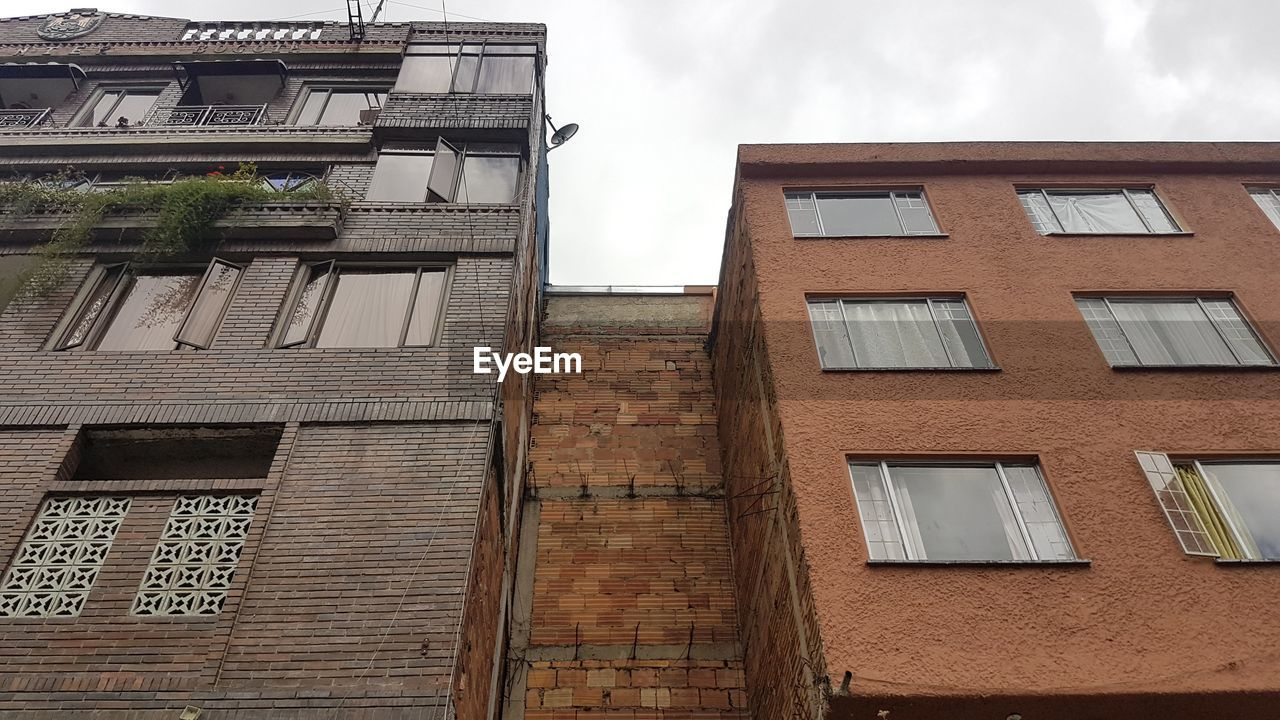built structure, architecture, building exterior, window, low angle view, building, residential district, no people, sky, day, outdoors, city, nature, cloud - sky, glass - material, brick, wall, fire escape, brick wall, house, apartment