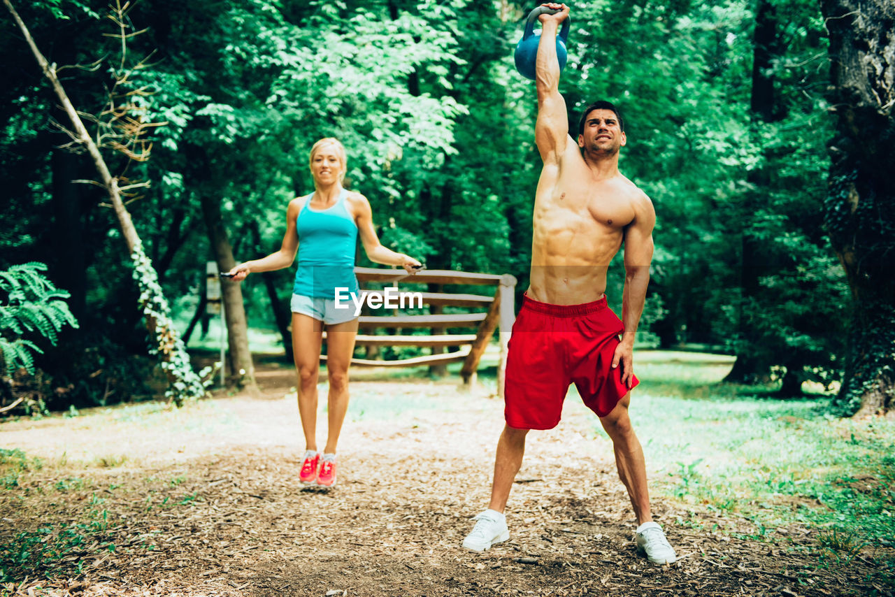 Full Length Of Shirtless Man With Woman Lifting Kettlebell On Field